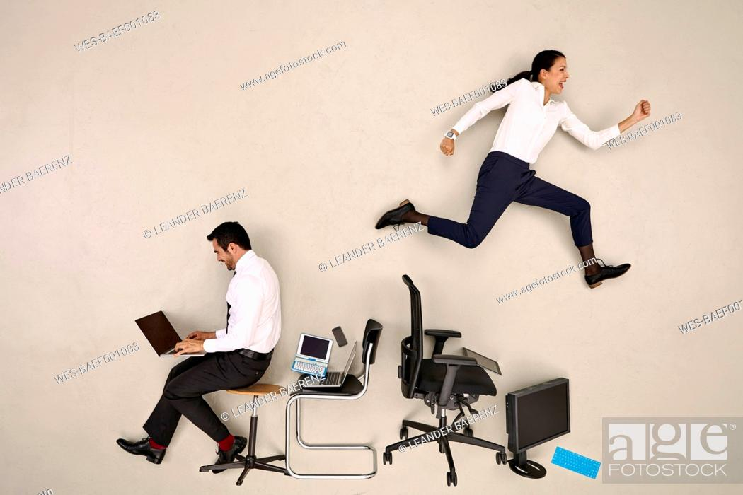 Stock Photo: Businessman sitting and working, female colleague jumping over chairs.