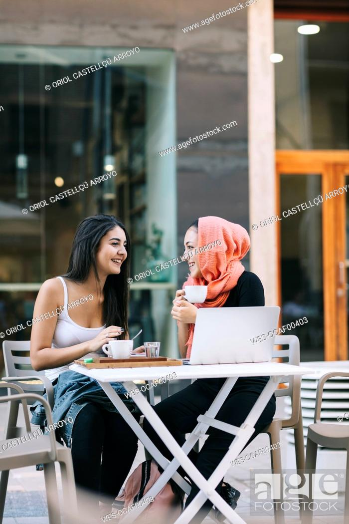 Stock Photo: Two happy friends sitting together at a pavement cafe with laptop.