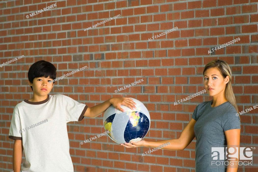 Stock Photo: Woman and boy holding globe wrapped in bandages, both looking at camera.