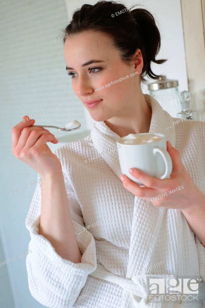 Imagen: Young woman drinking coffee in bathroom.