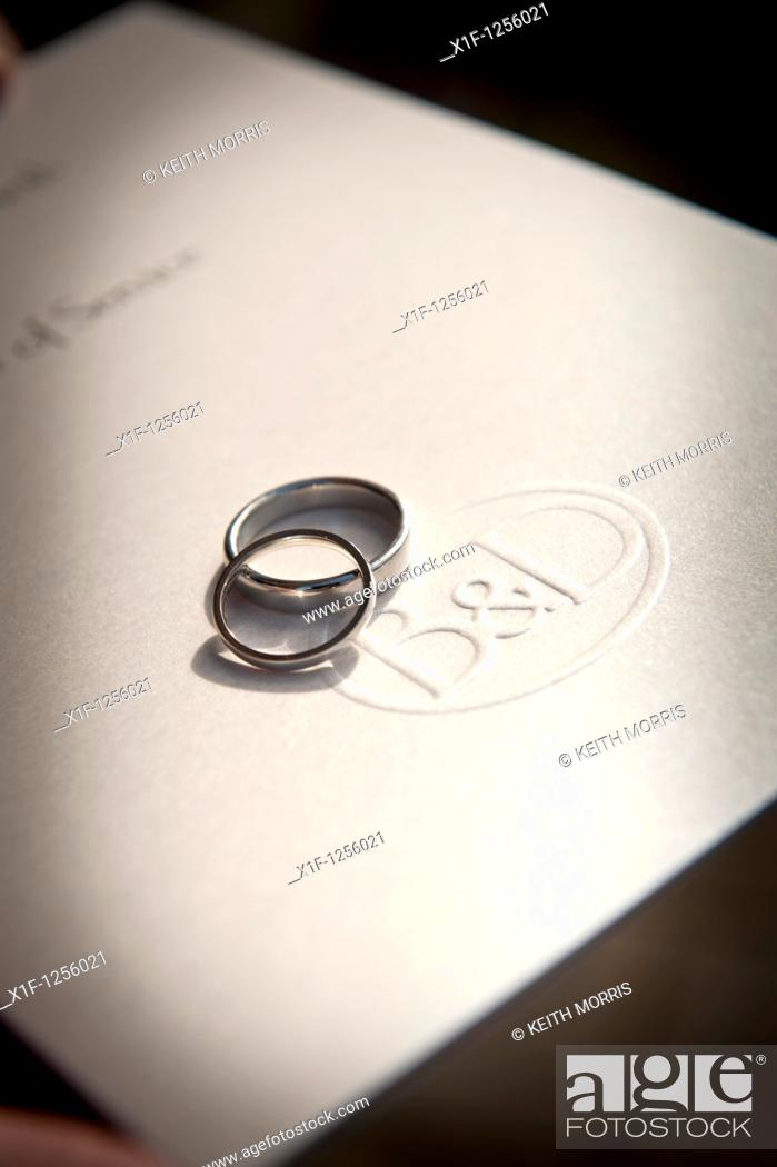 Stock Photo: intertwined wedding rings on a copy of the order of marriage service , UK.