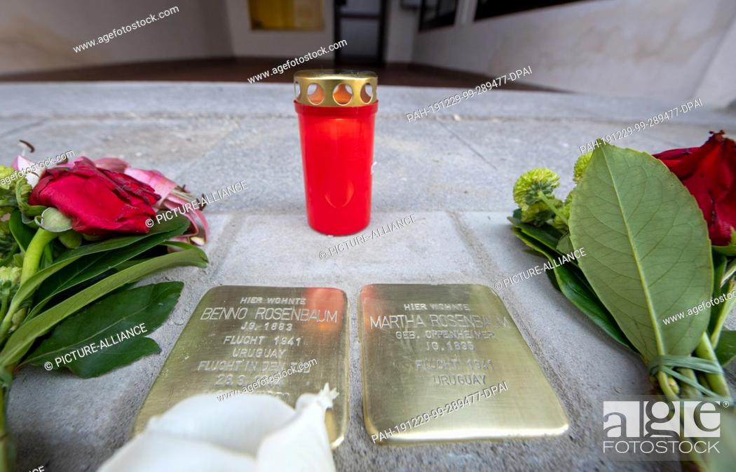 Stock Photo: 29 December 2019, Bavaria, Memmingen: Flowers lie next to the newly laid stumbling blocks for Benno and Martha Rosenbaum, behind which is a candle.
