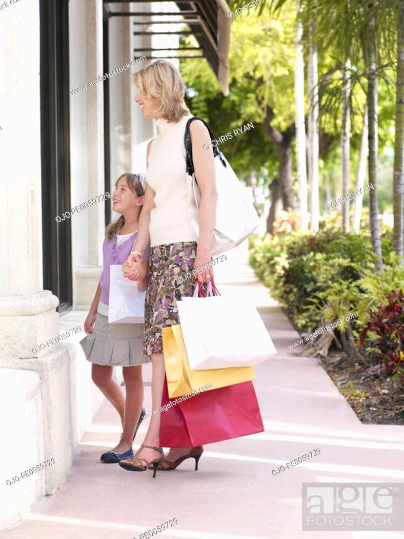 Stock Photo: Woman and young girl outdoors with shopping bags window shopping.