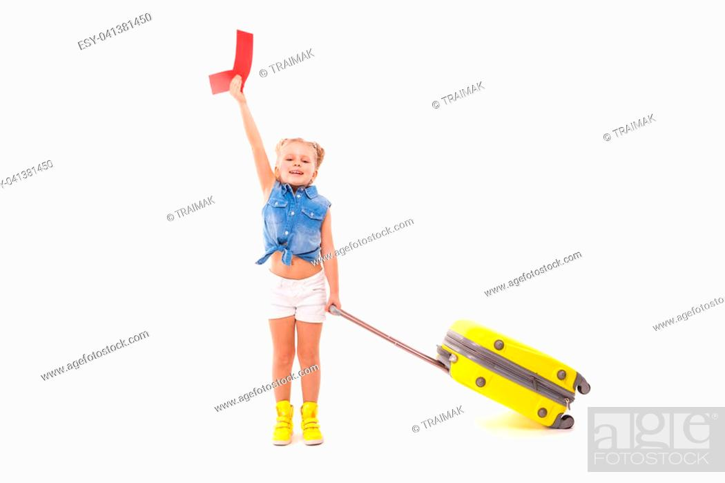 Stock Photo: Isolated on white, pretty caucasian blonde girl in blue shirt, white shorts, sunglasses and yellow boots hold yellow suitcase by the handle, look at camera.