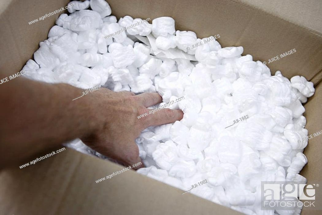 Stock Photo: Man filling box with packing foam, rear view, personal perspective, close-up.