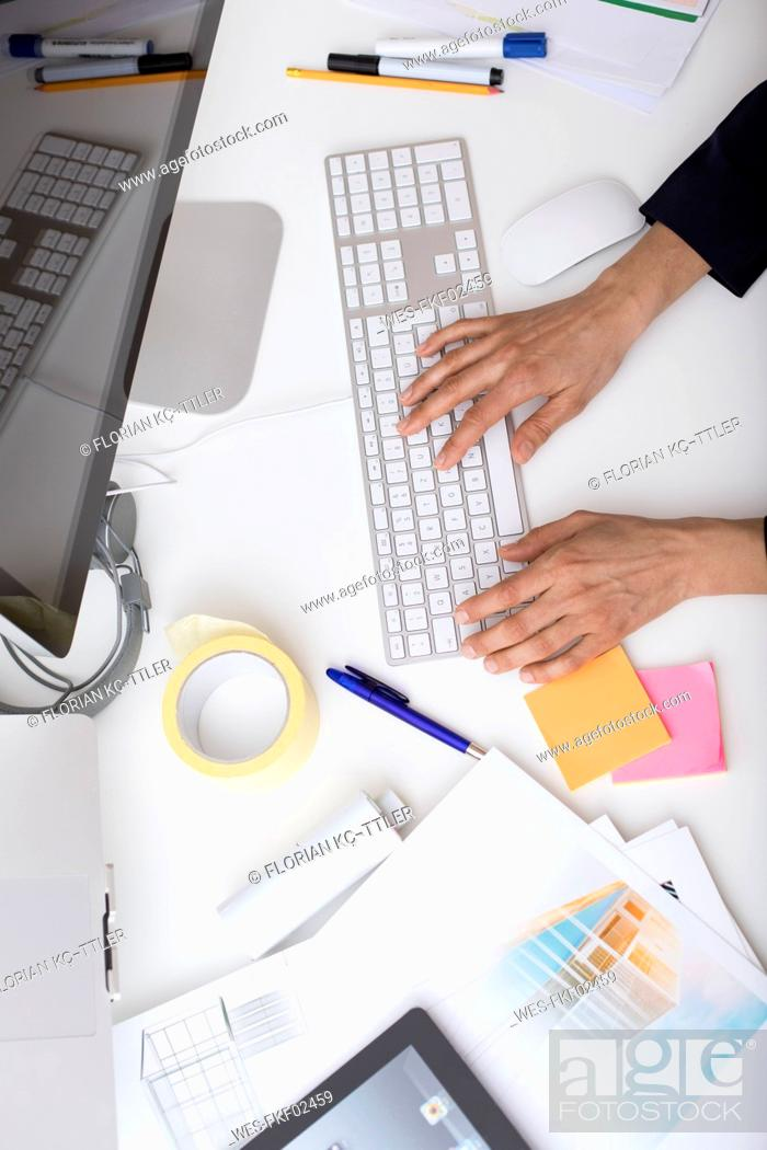 Stock Photo: Woman using computer keyboard at desk in office.