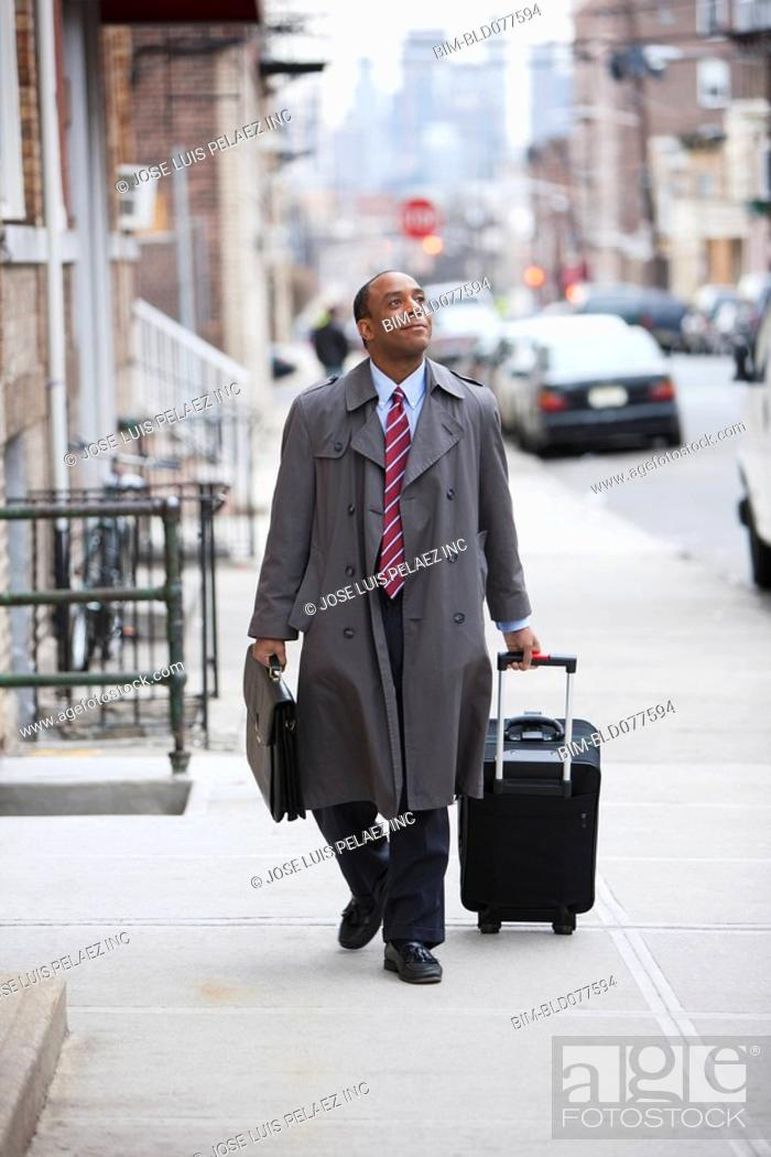 Stock Photo: African businessman pulling suitcase.
