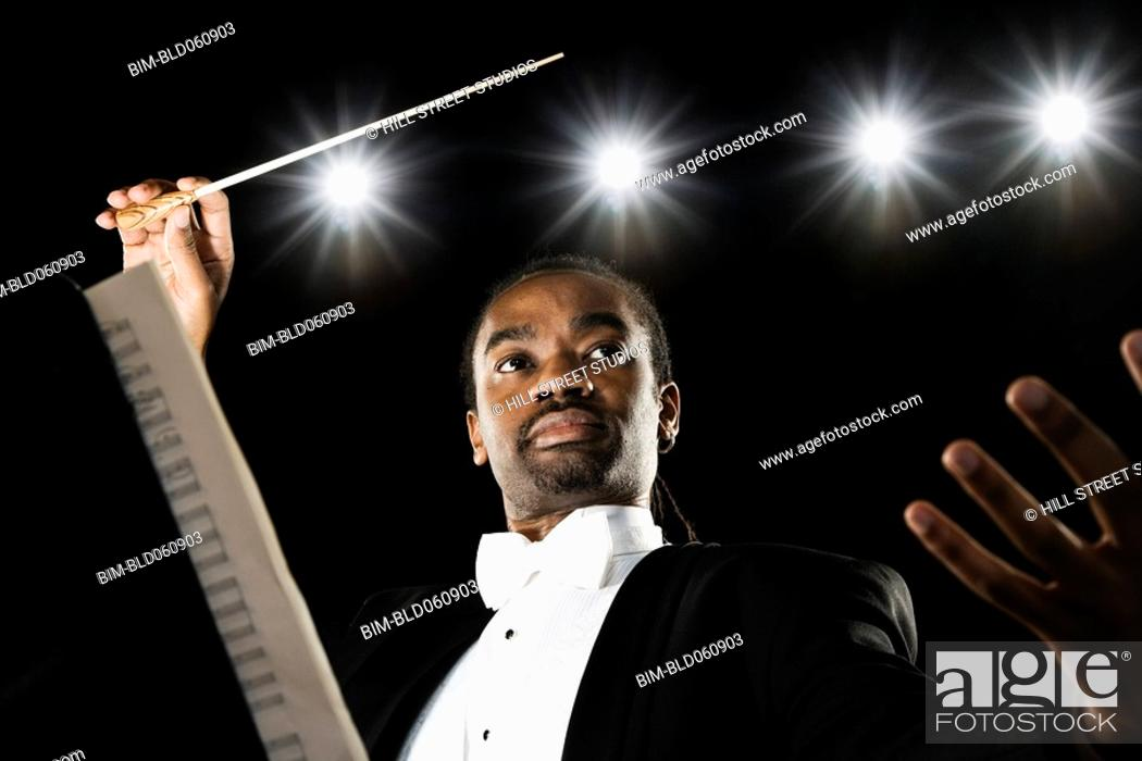 Stock Photo: African male conductor holding baton.