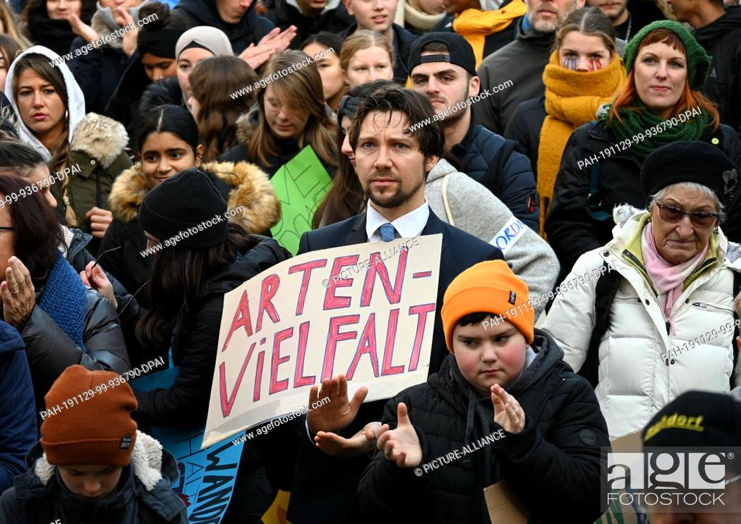 """Stock Photo: 29 November 2019, North Rhine-Westphalia, Cologne: A man holds a sign with the inscription """"""""Biodiversity"""""""" at a demonstration for climate protection."""