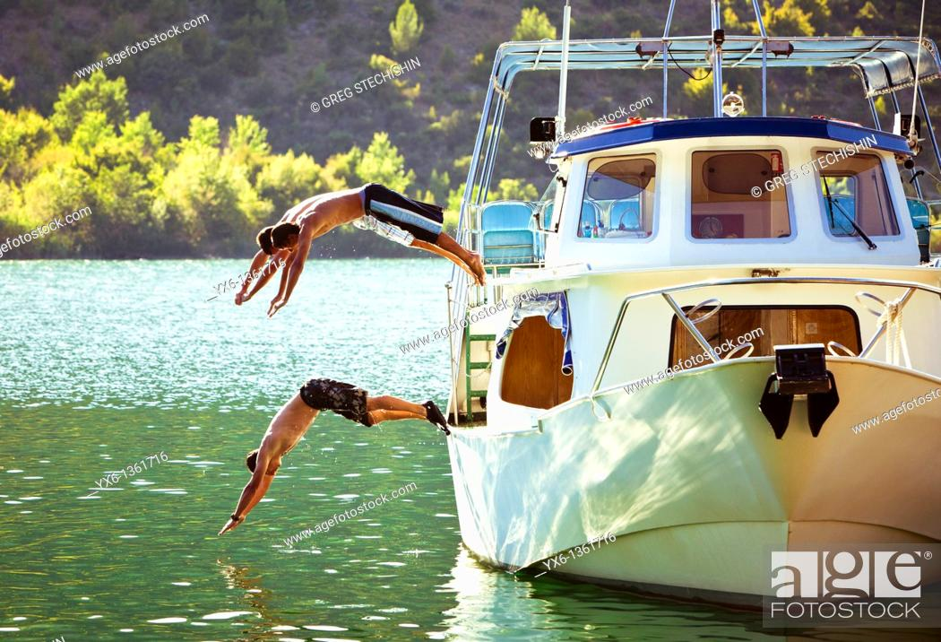 Stock Photo: Three men diving into the Krka River in the Krka National Park on a hot summer day in Croatia.