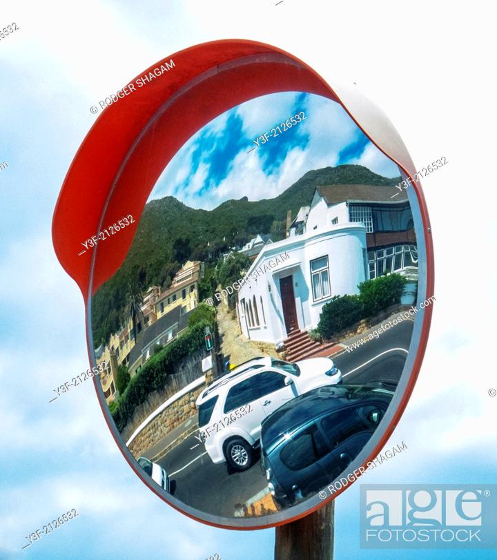 """Stock Photo: A pole-mounted mirror at an obscured intersection, allows drivers to see """"around the corner""""."""