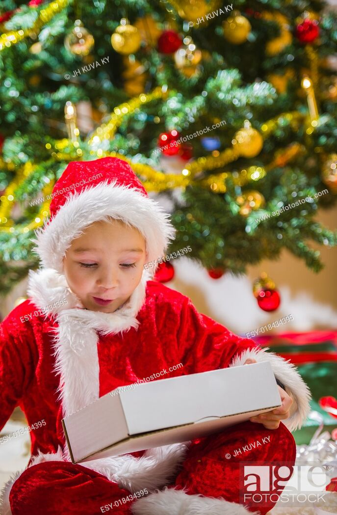 Stock Photo: Surprised boy opens a Christmas gift, Christmas tree and gifts on background.