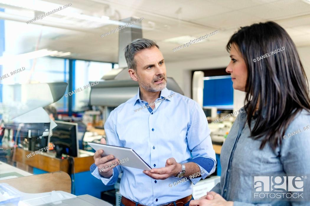 Stock Photo: Businessman with tablet and businesswoman having a work meeting in a factory.