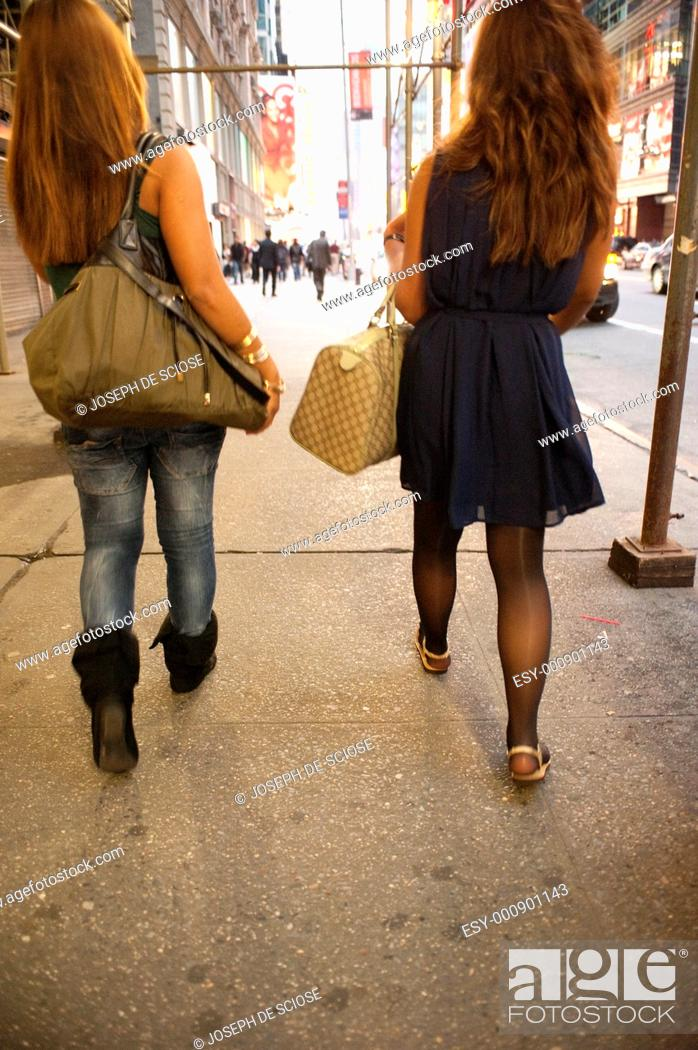 Stock Photo: Two young female tourists walking in Times Square, New York City, backs to the camera.