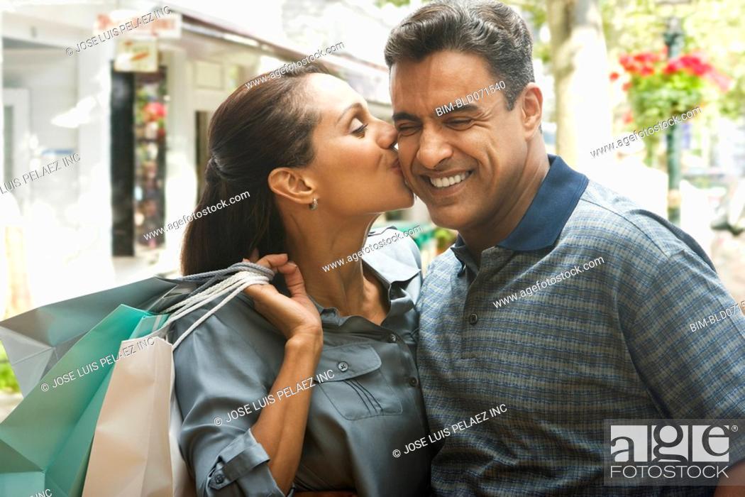 Stock Photo: Hispanic woman kissing husband on cheek.