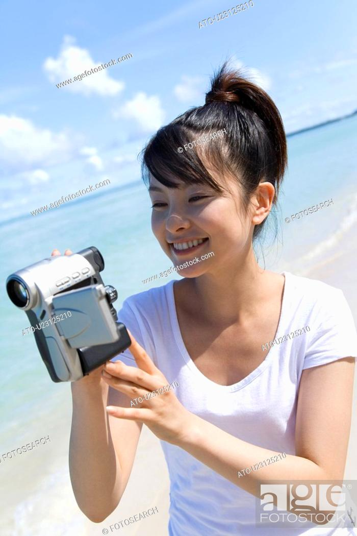 Stock Photo: Young woman holding video camera on beach, smiling, Saipan, USA.