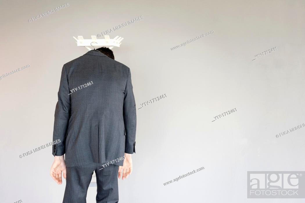 Stock Photo: Businessman left behind on a coat hanger.