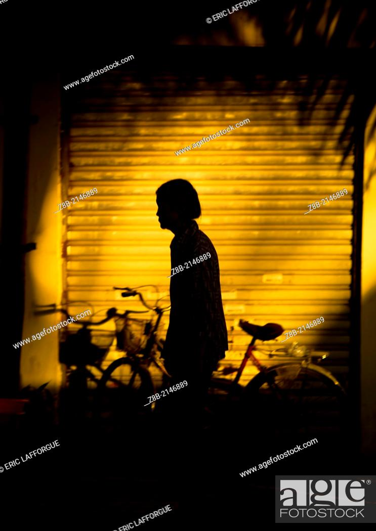Stock Photo: Silhouette Of A Woman In The Street, Menglun, Yunnan Province, China.
