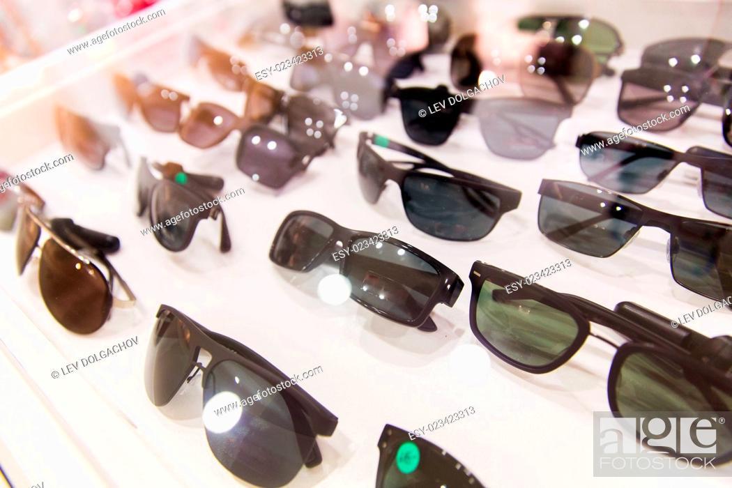 Stock Photo: optics, accessory and fashion concept - close up of sunglasses at optician.