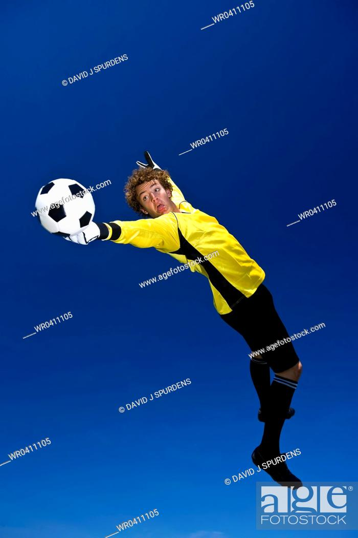Stock Photo: A goalkeeper stretches to make a save.