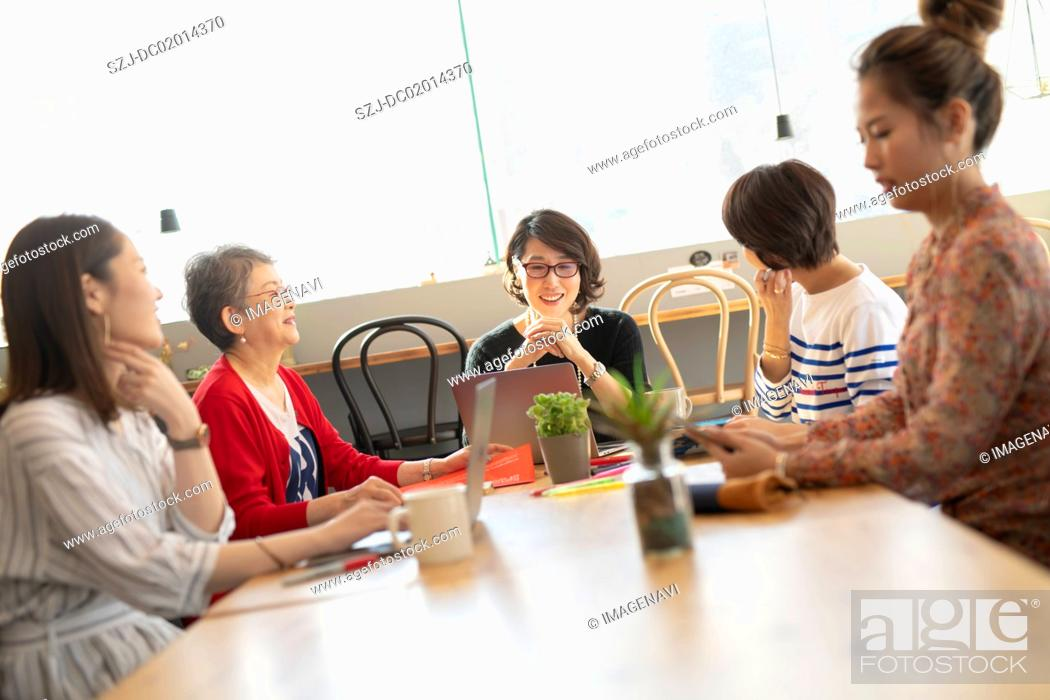Stock Photo: Five women in coworking office space.