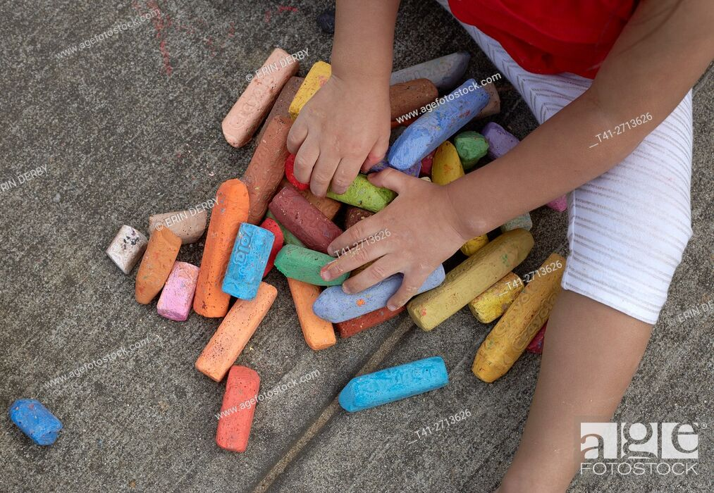 Stock Photo: baby playing with chalk outside on concrete.