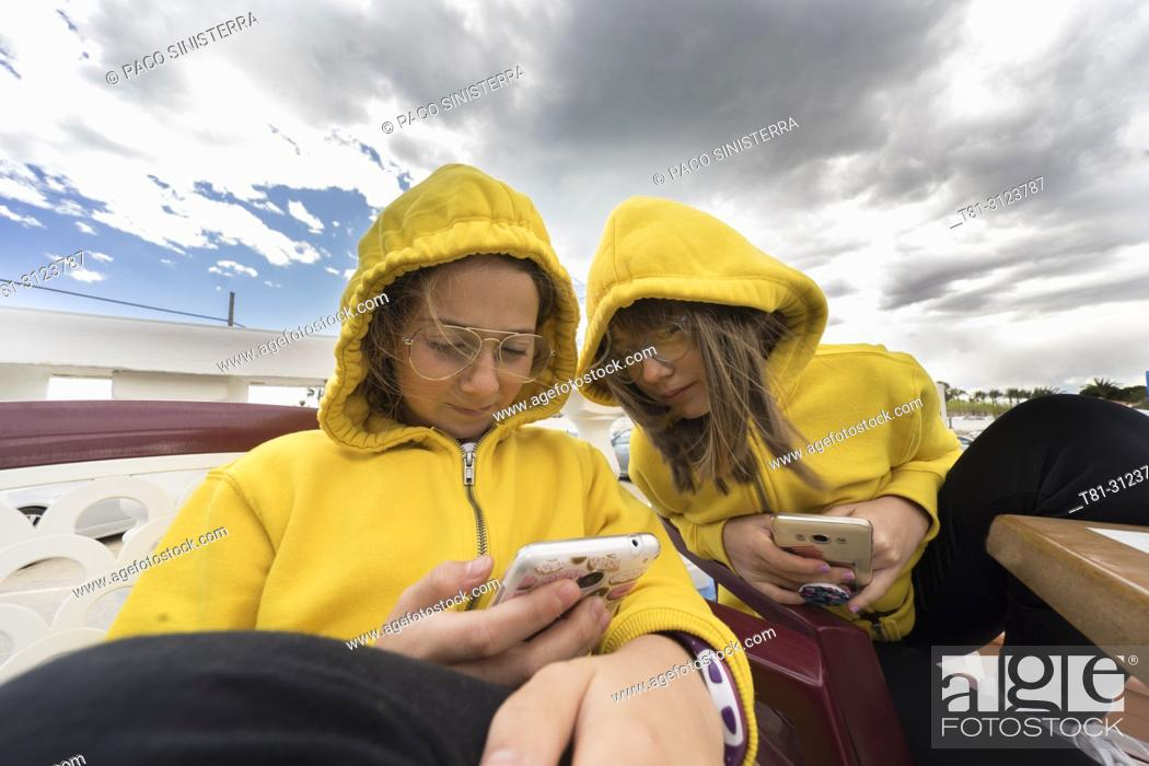 Stock Photo: girls looking at a mobile phone at the beach of Alcocebre, Castellon, Spain.