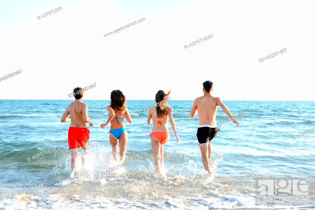 Stock Photo: four happy friends young people man and woman having fun at ocean beach jumping together in the sea.