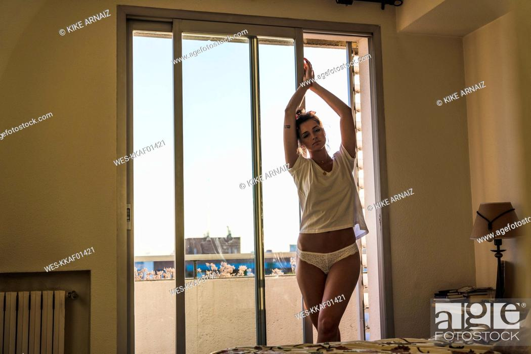 Stock Photo: Young woman in t-shirt and panties at home standing at the window.