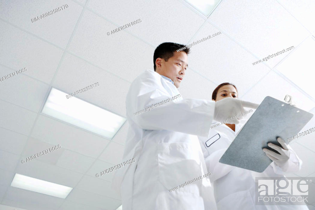 Stock Photo: Low angle view of two technicians looking at clipboard.