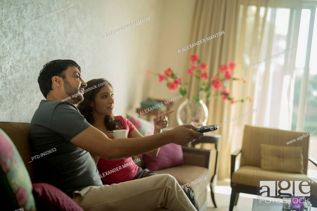 Stock Photo: Man and woman on sofa using television remote.