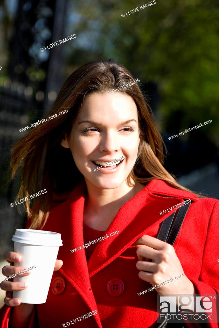 Stock Photo: A young woman in a red coat holding a hot drink.