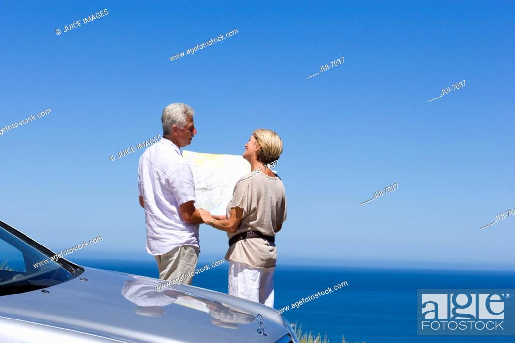 Stock Photo: Senior couple standing beside parked car on clifftop overlooking Atlantic Ocean, consulting map, rear view.