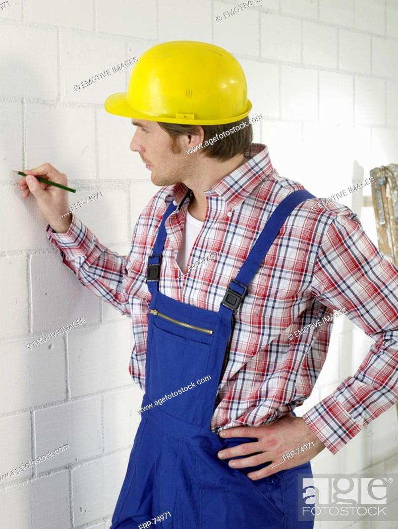 Stock Photo: Construction worker is marking with a pencil on the wall.