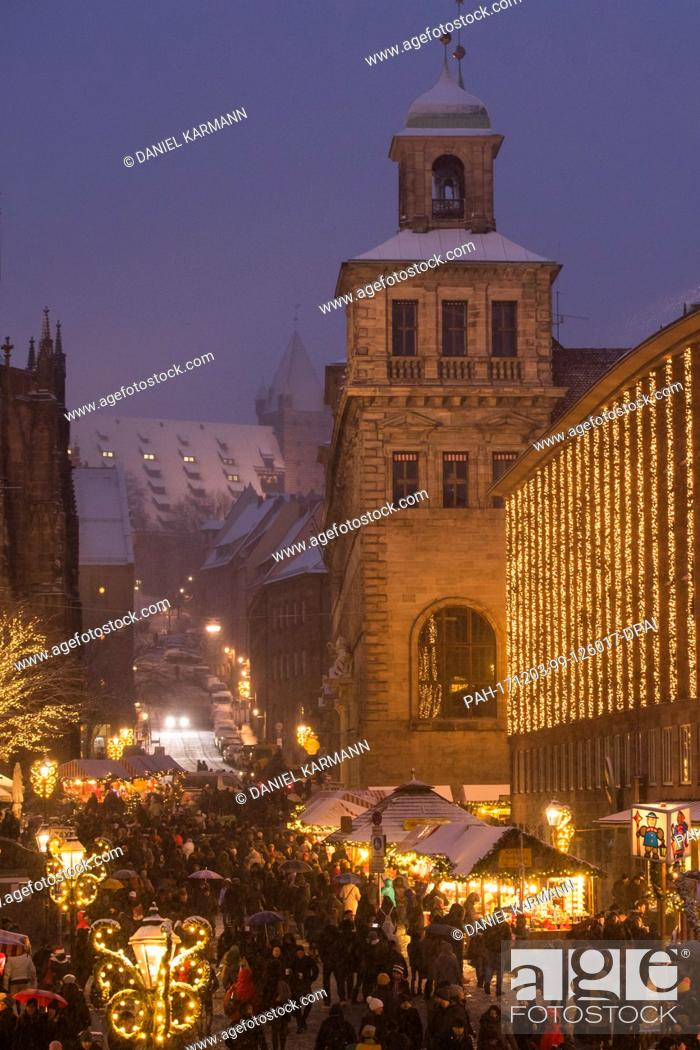 Stock Photo: Visitors walk across the Christkindlesmarkt during snowfall in Nuremberg, Germany, 03 December 2017. Photo: Daniel Karmann/dpa.