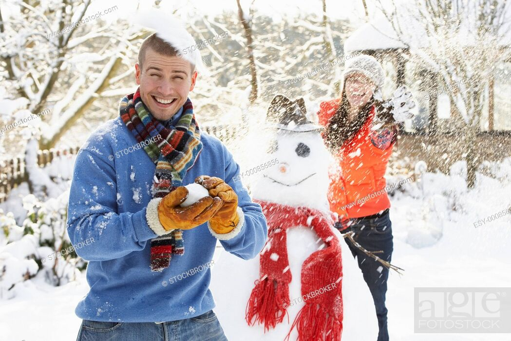 Stock Photo: Young Couple Having Snowball Fight In Garden.