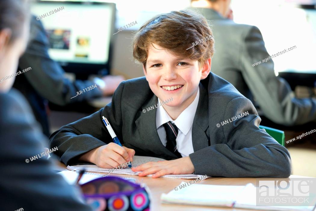 Stock Photo: Portrait smiling middle school student doing homework in study hall.