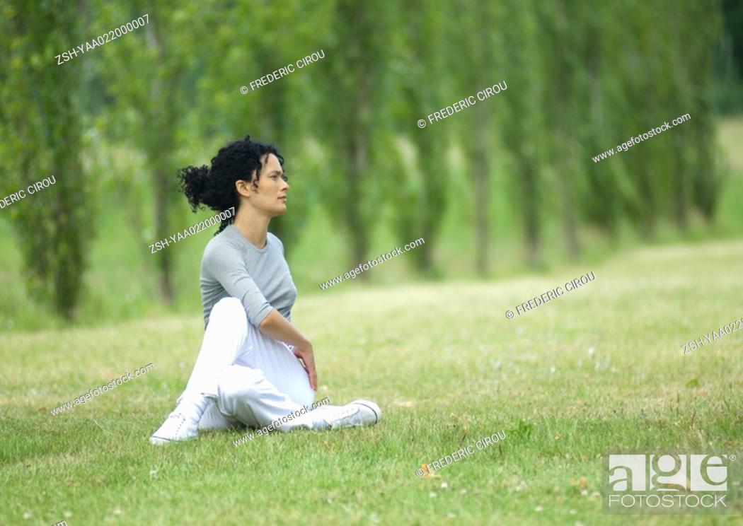 Stock Photo: Young woman stretching on grass.