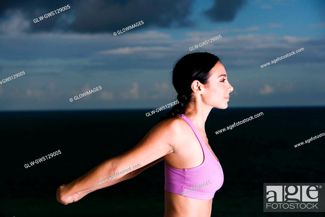 Stock Photo: Side profile of a young woman meditating.