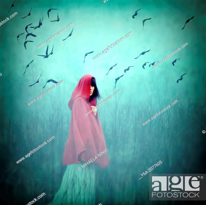 Stock Photo: Woman wearing red cloak walking in to dense fog.