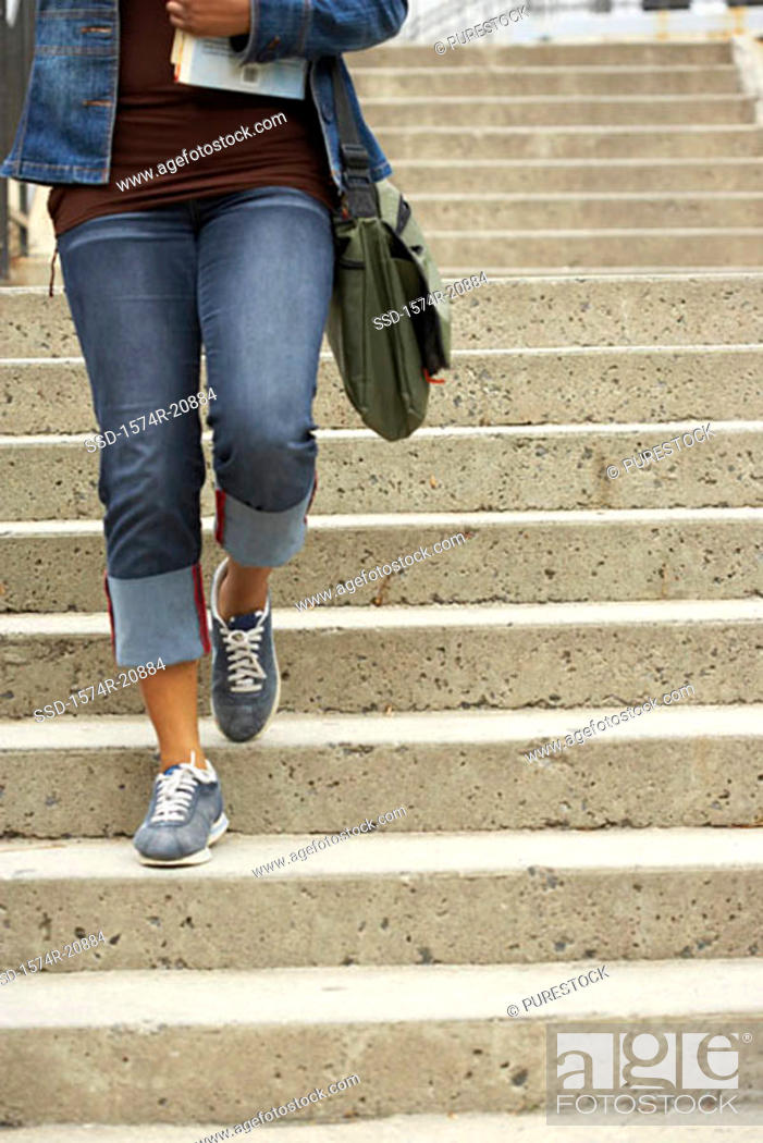 Stock Photo: Low section view of a college student moving down a staircase and carrying books.