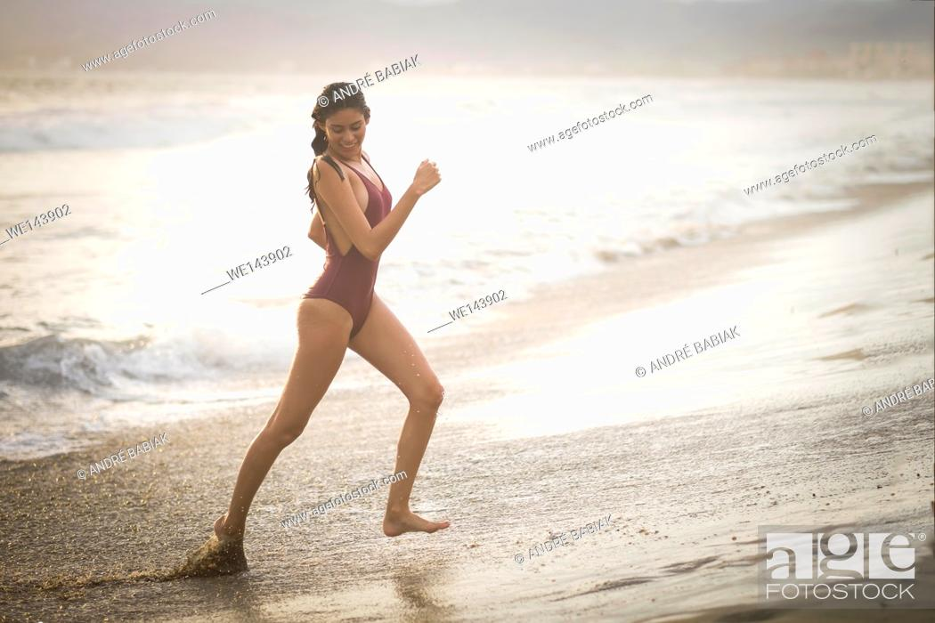 Stock Photo: Young attractive woman in swimsuit running at the beach before sunset hour.