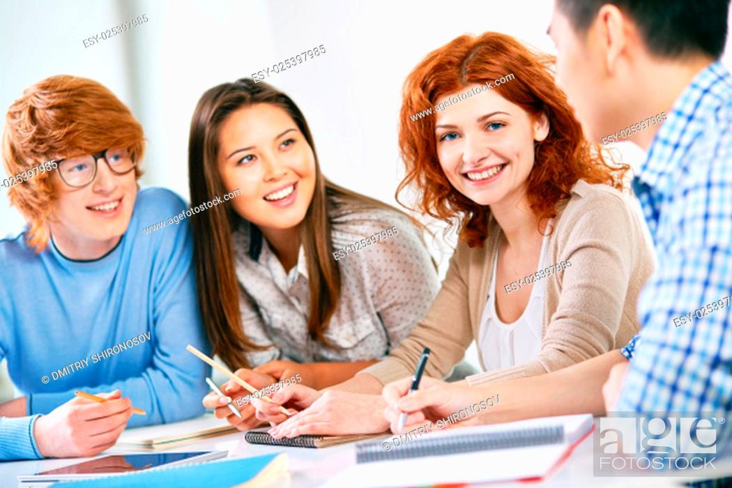 Stock Photo: Smart teenage student looking at camera while her groupmates discussing something.