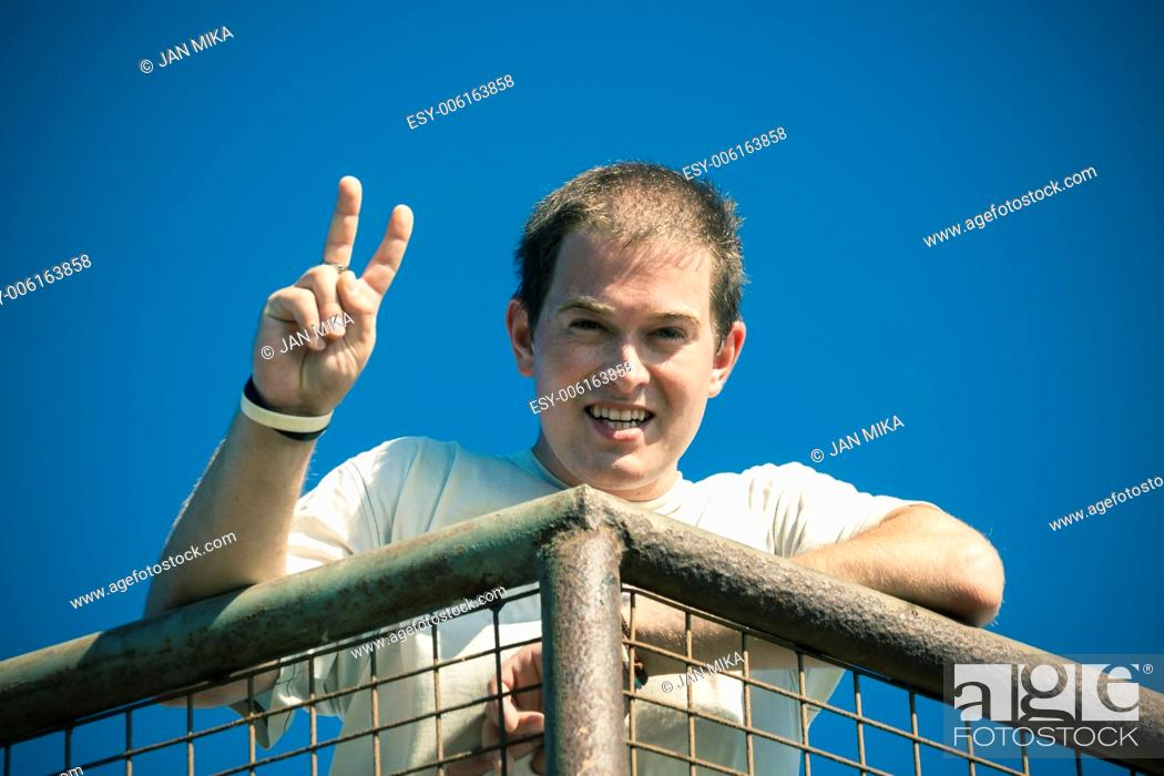 Stock Photo: Young happy man gesturing v sign.