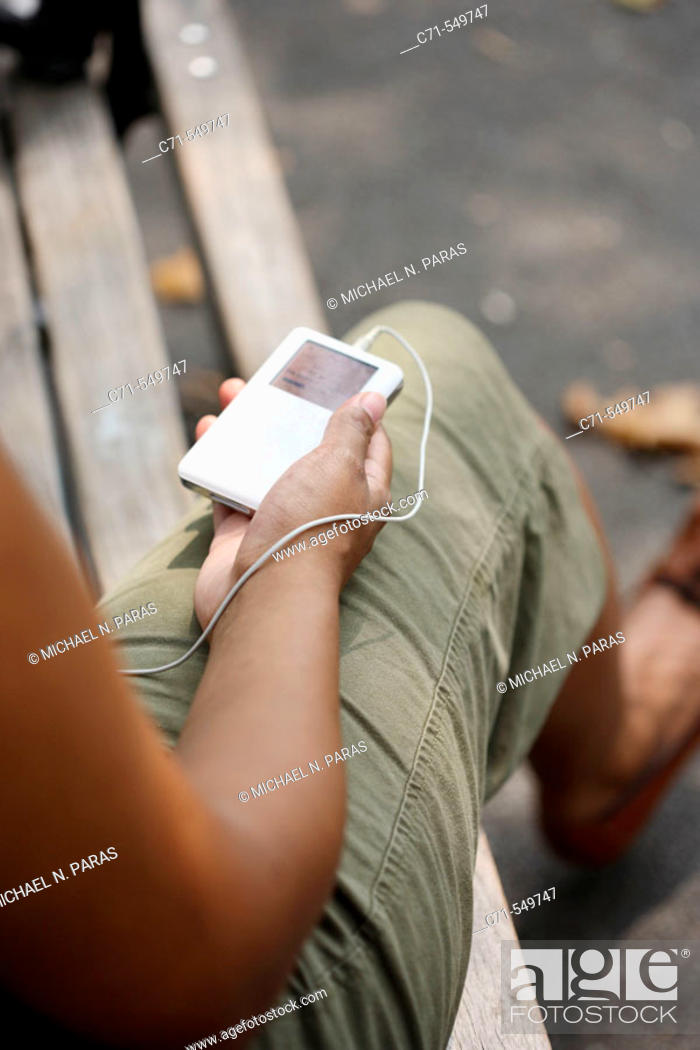 Stock Photo: African-American woman holding ipod on park bench.