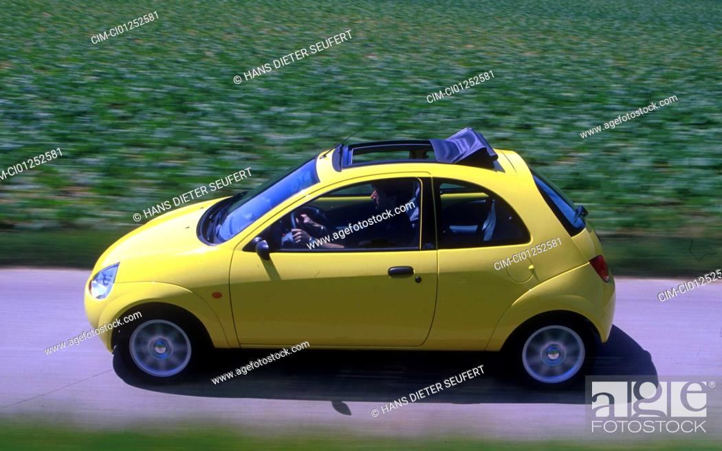 Stock Photo Car Ford Ka  I Small Approx Limousine Model Year   Yellow Driving Diagonal From The Front Oben Side View Country Road