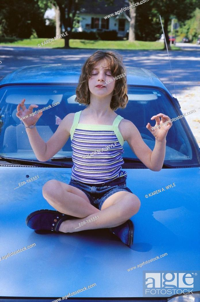 Stock Photo: Girl about 9 years old in tank top and shorts sitting cross-legged on hood of light blue car with eyes closed, arms out to sides with elbows bent.
