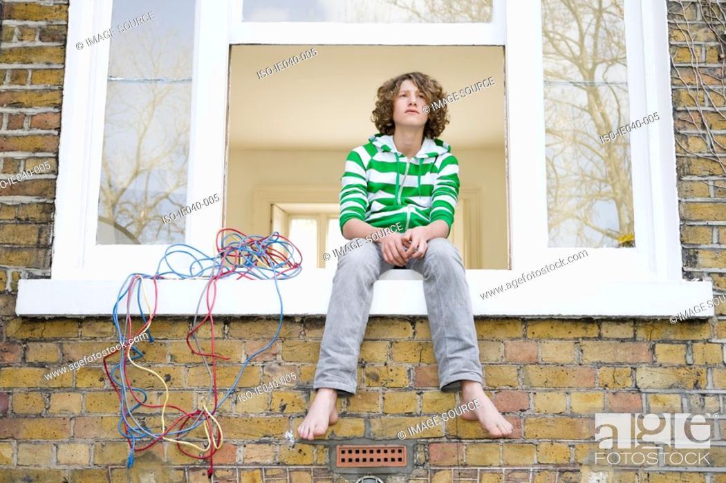 Stock Photo: Teenage boy sat on windowsill.