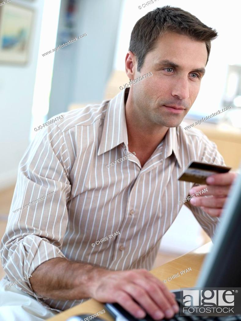 Stock Photo: Man sitting at computer with credit card.