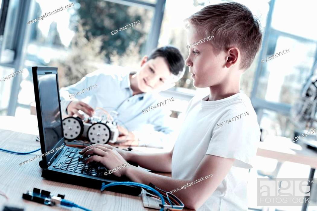 Stock Photo: Innovative generation. Side view on a completely absorbed in the process youngster working on a laptop and programming after designing a new robotic machine.